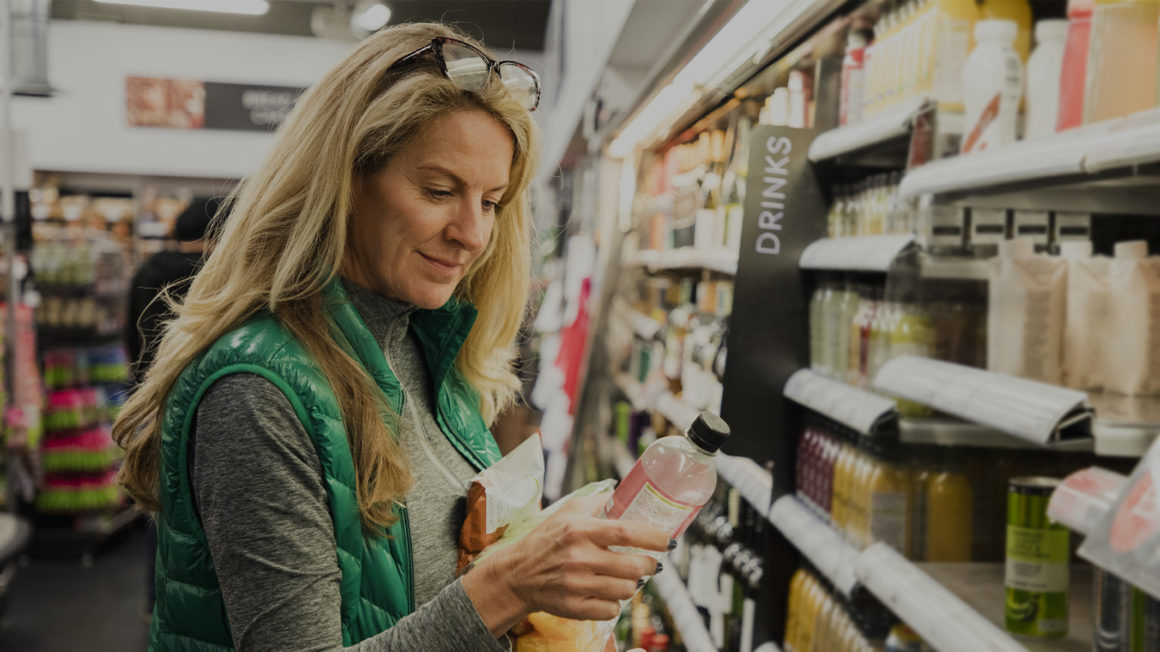 woman looking at product label in grocery store