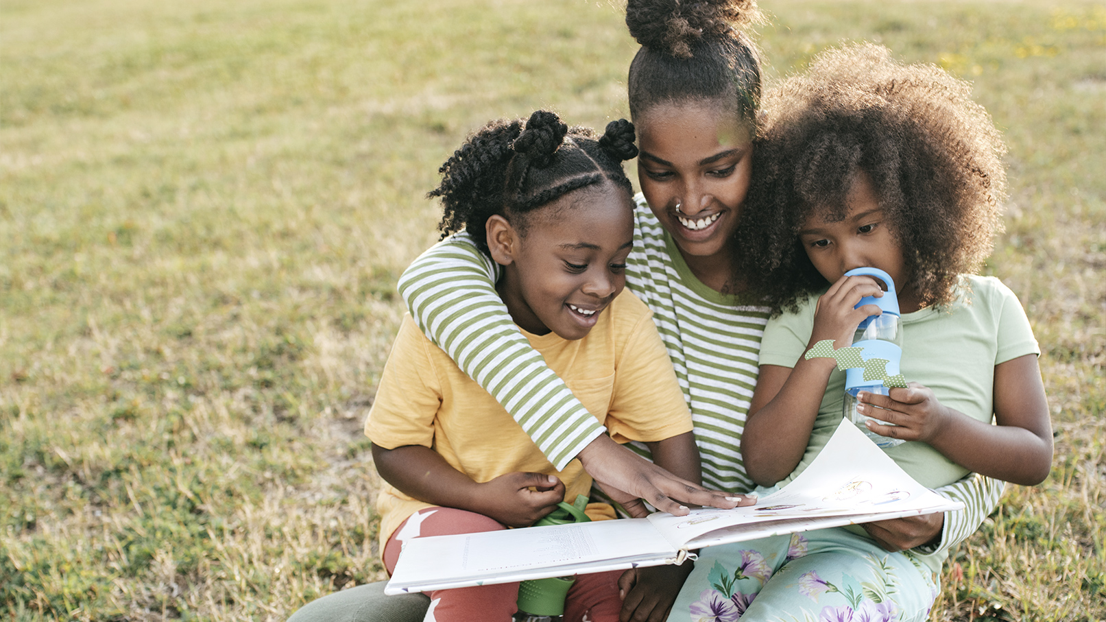 Mother reading to two daughters outside