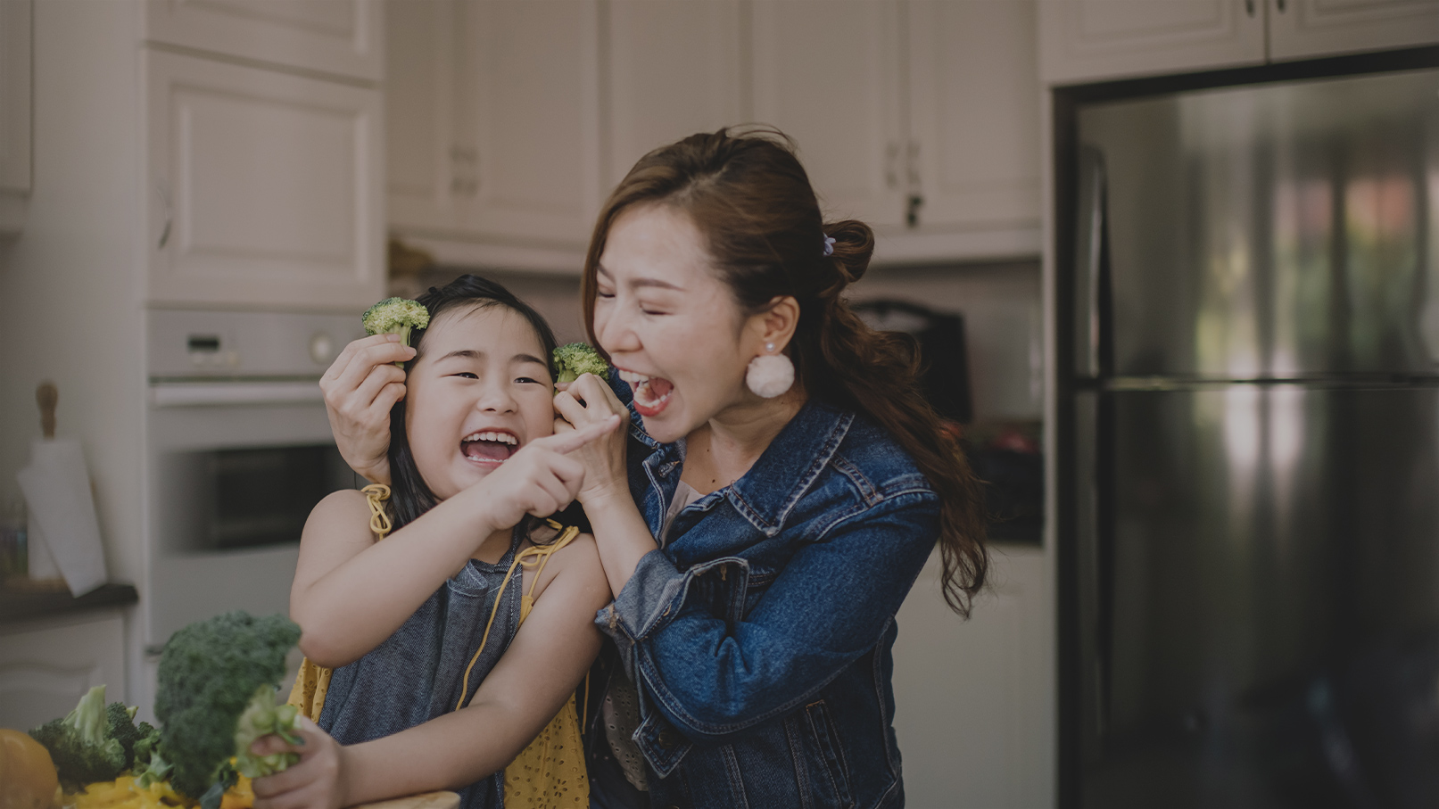 Mom and daughter cooking broccoli