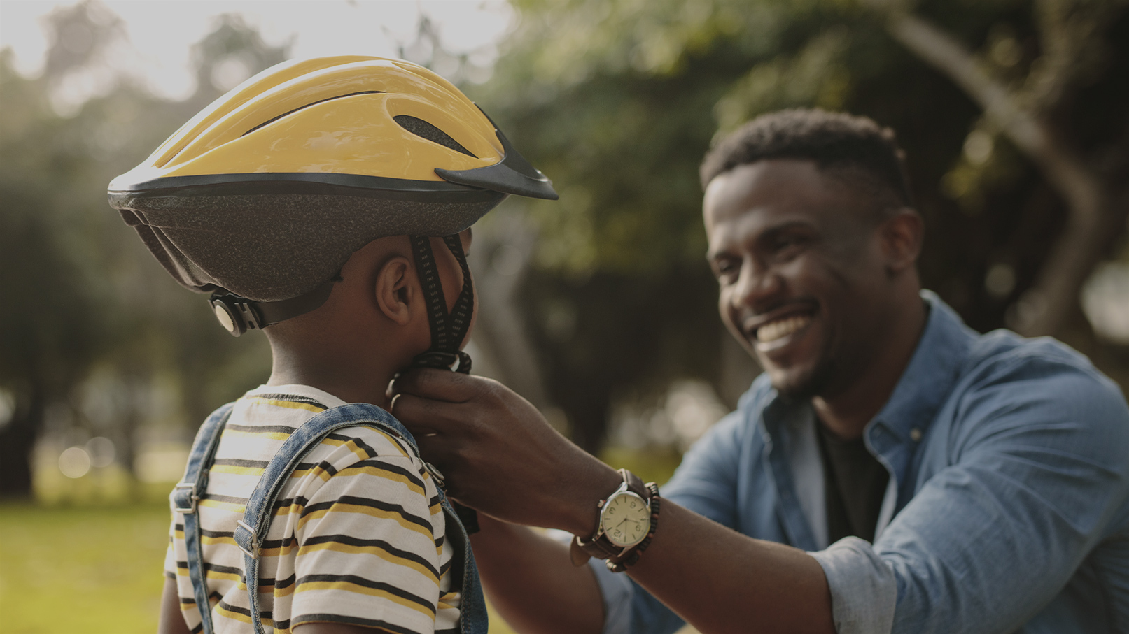 Father practicing safe & fun summer activities with son - buckling bicycle helmet